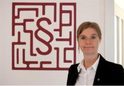 Sabine Mayer vor ihrem Logo